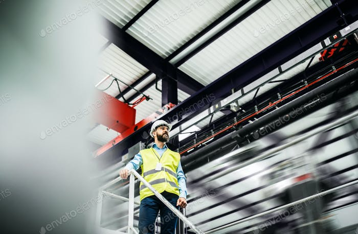A low angle view of an industrial man engineer standing in a factory.
