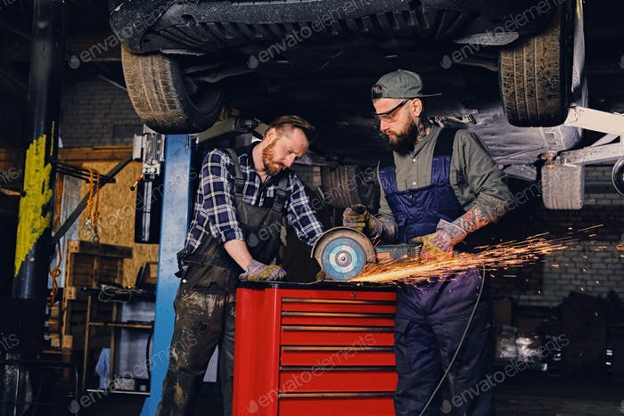 Two b mechanics working with an angle grinder in a garage.