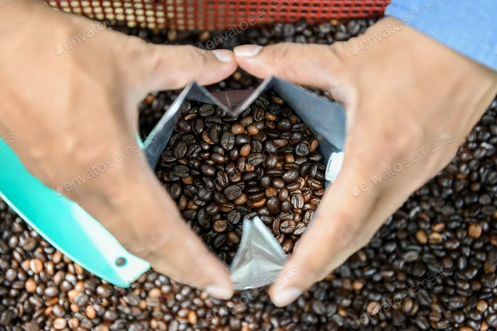 Coffee beans in bag with hand holding bag.