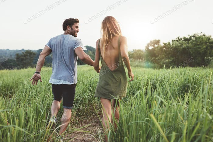Young couple walking through grassy field