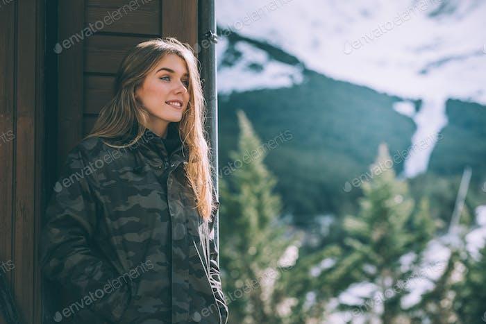 Porträt Junge hübsche Frau im Winter im Schnee in einem Blockhaus aus Holz