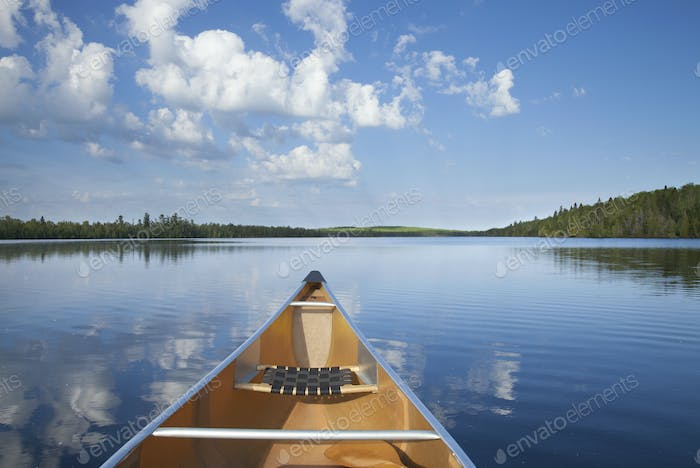 Canoe on calm northern Minnesota lake in the morning during summer