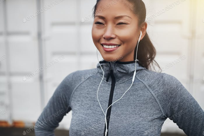 Sporty young Asian woman standing outside before a run