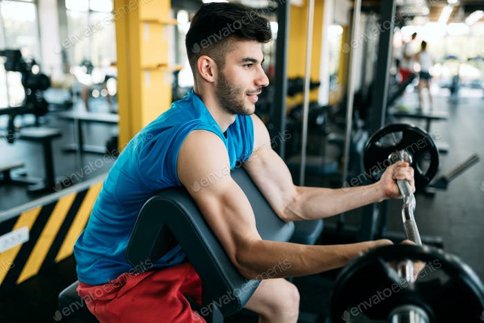 Young attractive man doing exercises in gym