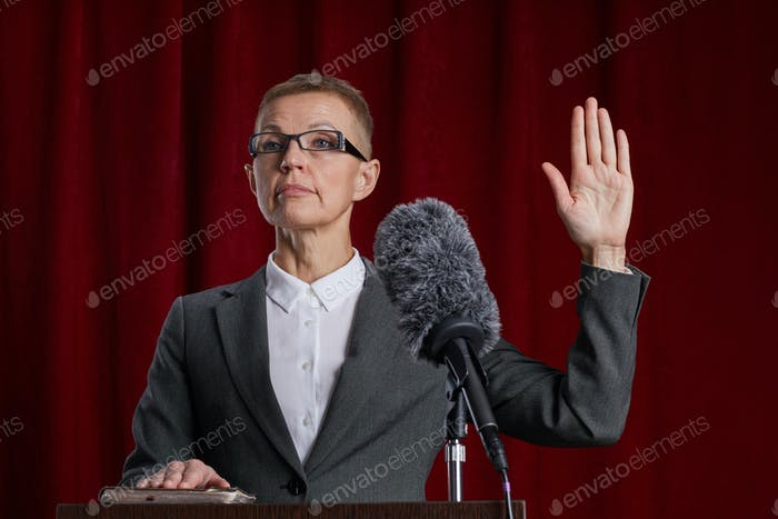 Mature Female Official Speaking on Stage