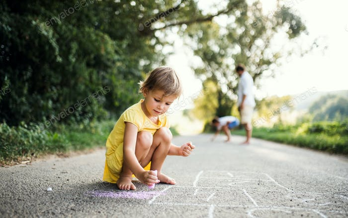 Small cute girl on a road in countryside in sunny summer nature, drawing with chalk.