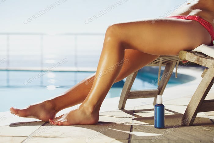 Young woman sunbathing by the poolside