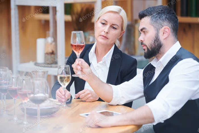 Serious and attentive sommeliers evaluating color of wine sample