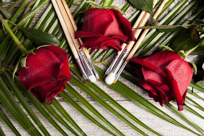 Makeup brushes next to roses