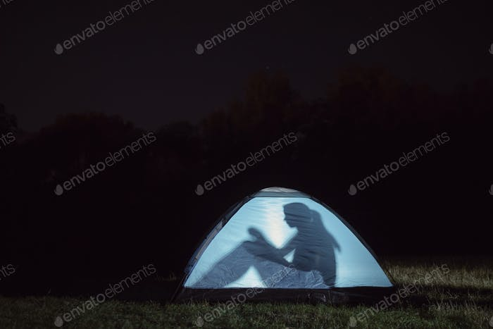 A silhouette of a girl sitting in a tent outdoors at night.