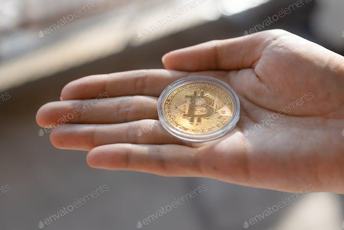 Joven sosteniendo el token Bitcoin BTC en la palma de la mano