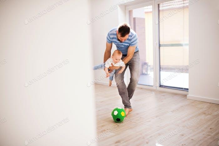 Junger Vater mit einem kleinen Sohn zu Hause spielt mit einem Ball.