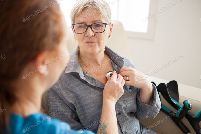 Back view of nurse listening old woman heart beat