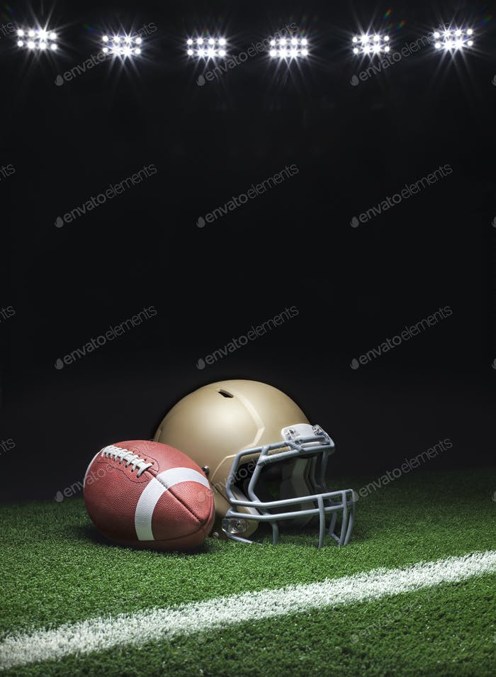 Football and helmet on grass field with stripe under lights at night