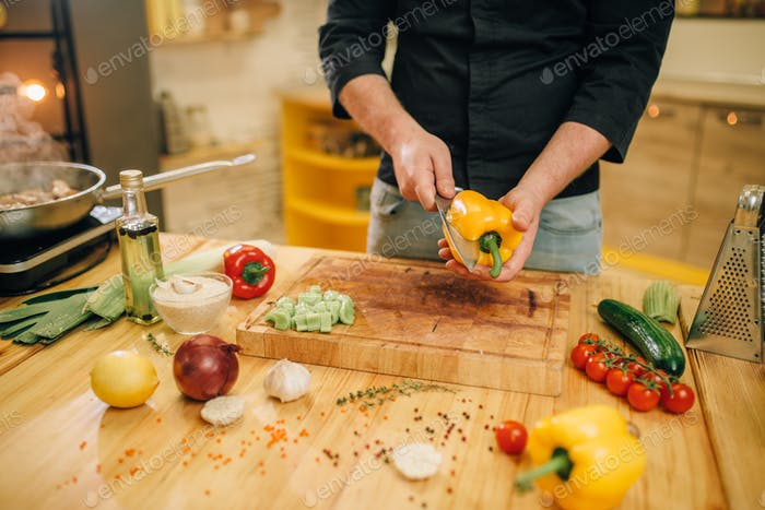 Chef mit Messer schneidet gelben Pfeffer auf Holzbrett