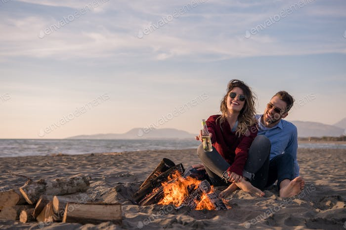 Young Couple Sitting On The Beach beside Campfire drinking beer