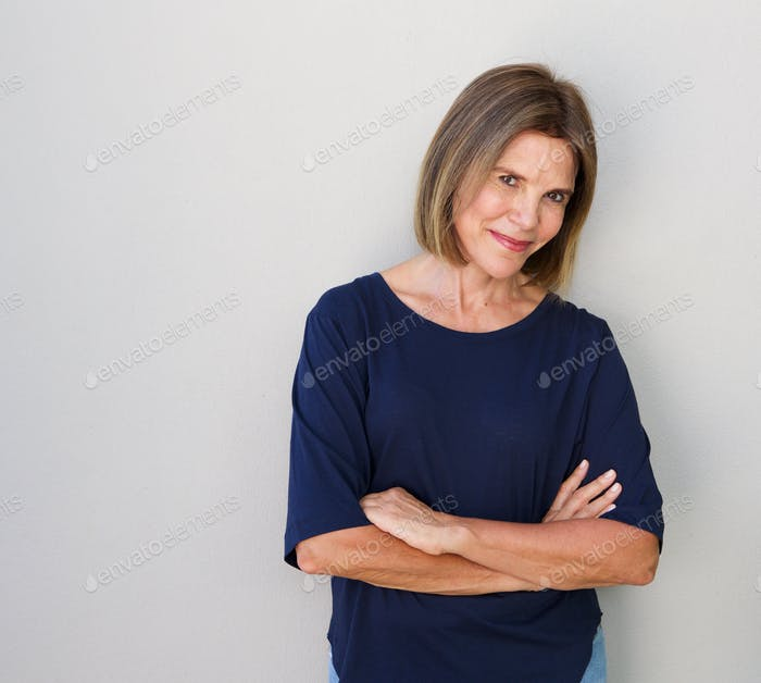senior woman smiling against gray wall