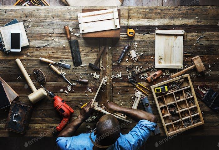 Luftaufnahme des Zimmermannes, der mit Werkzeugen Ausrüstung set arbeitet