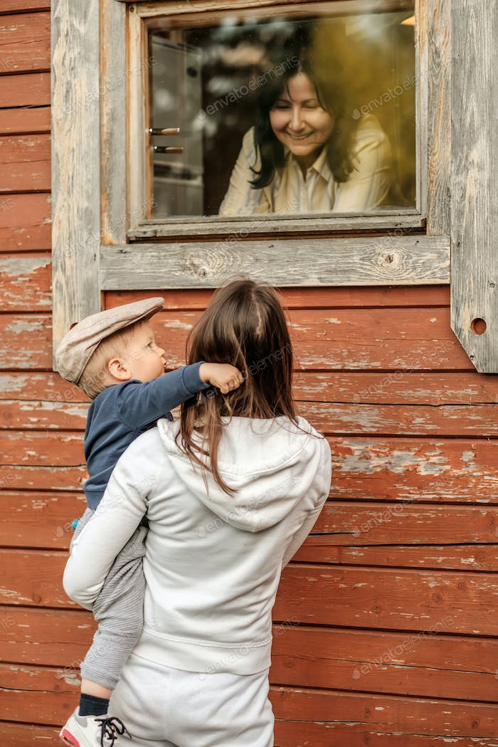 One year old baby boy with his mother outdoors looking at window