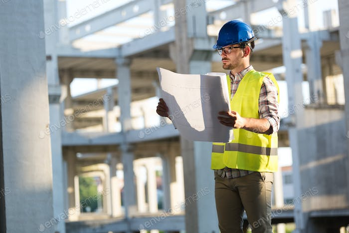 Engineers working on a building site with blue prints
