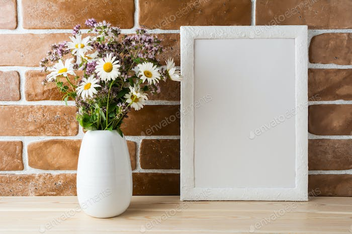 White frame mockup with wildflowers bouquet near exposed brick w