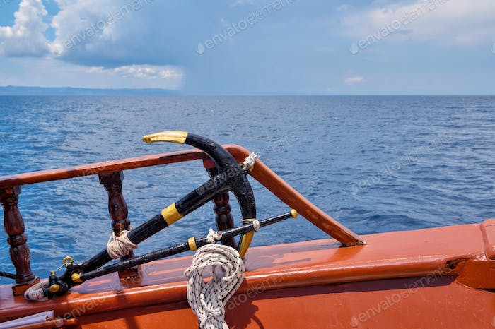 A anchor and deck of a wooden antique sailing yacht against the