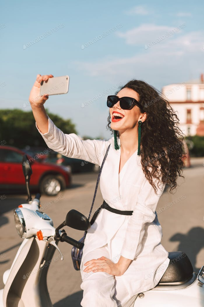 Young cheerful woman in suite and sunglasses sitting on moped happily taking selfie on city street
