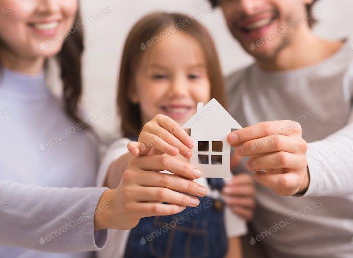 Cutout Papierhaus in den Händen der glücklichen Familie von drei