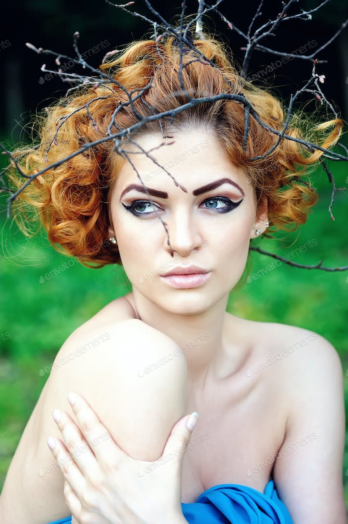 Fashion Model Woman Portrait with Curly Red Hair on Wood Branche