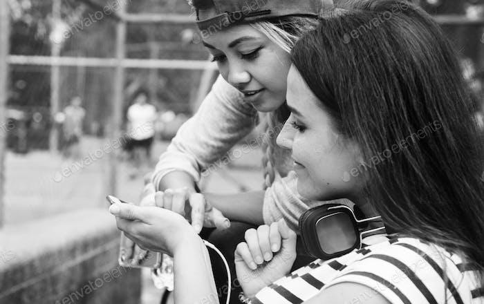 Junge erwachsene weibliche Freunde hören Musik durch ihre smar