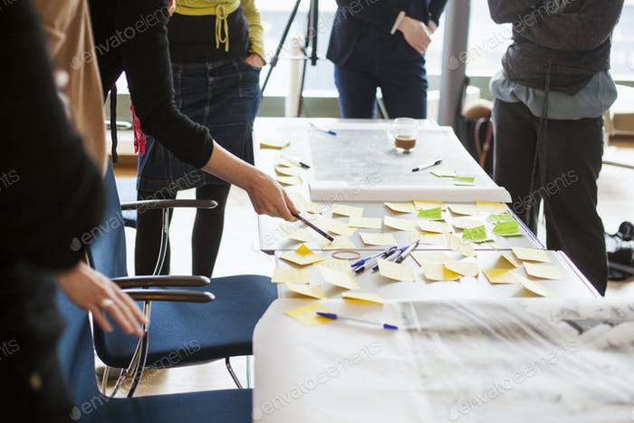 Cropped image of business people strategizing with sticky notes in office