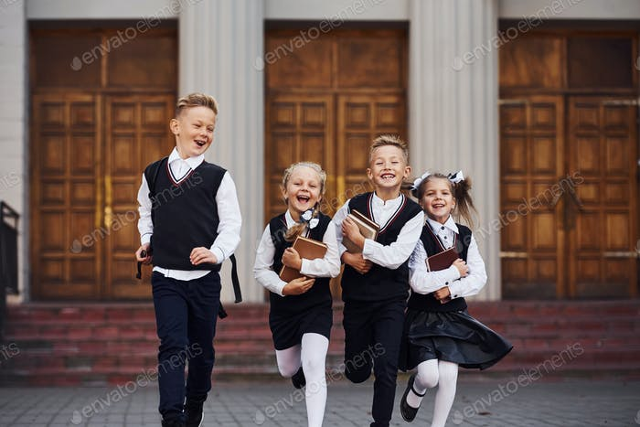 Group of kids in school uniform that is running outdoors together