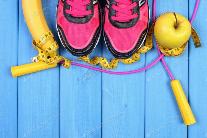 Pair of sport shoes, fresh fruits and accessories for fitness on blue boards, copy space for text