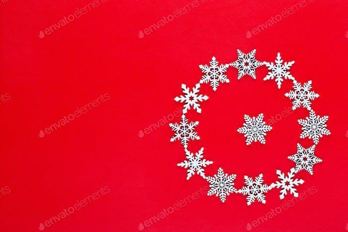 Weiße Schneeflocken Kranz Dekorationen auf rotem Hintergrund.