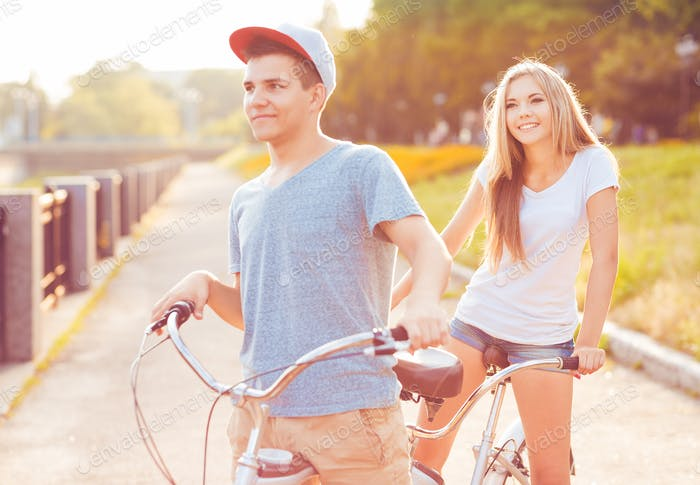 Happy couple - man and woman riding a bicycle in the park outdoo