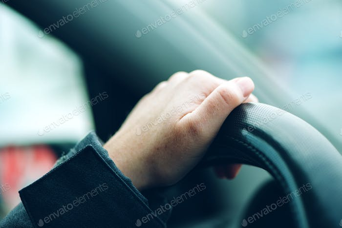 Female hand on car steering wheel