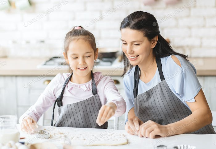 Pretty little girl and her attractive mom preparing pastry together