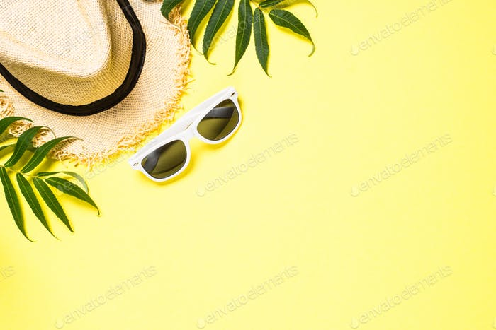 Summer hat and sunglasses on yellow top view.