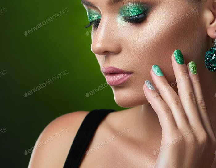 Hübsches Mädchen mit perfekter Bronze-Haut, glänzende Maniküre, grünes Make-up