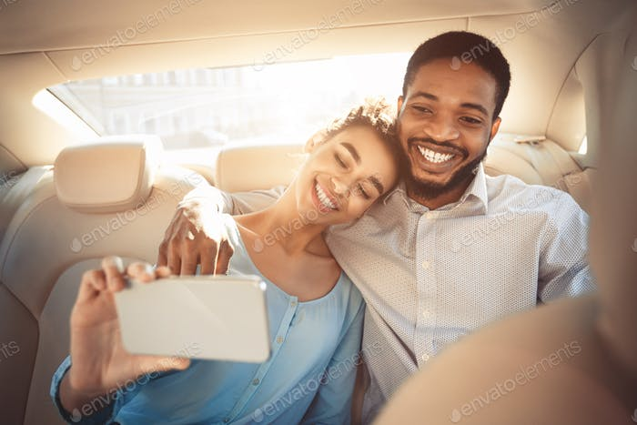 Happy afro couple taking selfie in new car