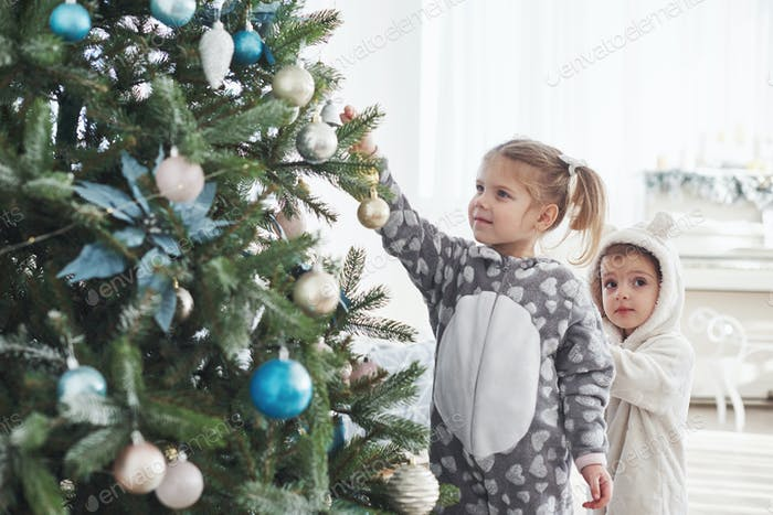 Young girls helping decorating the Christmas tree, holding some Christmas baubles in her hand