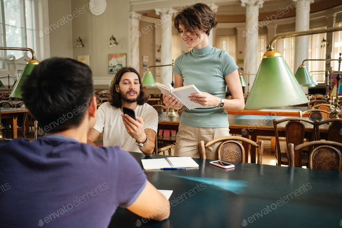 Group of young casual students happily studying together in library of university