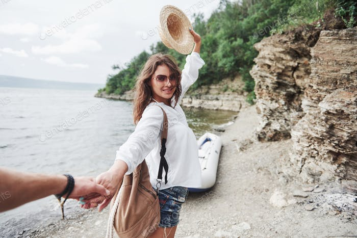 Portrait of happy young woman in hat holding man by hand and going to the boat on the lake in the