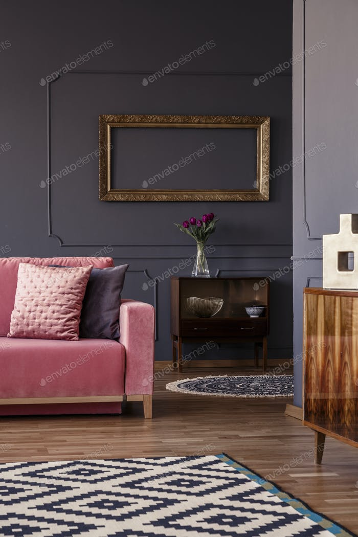 Decorative pillows on pink couch standing in dark living room in