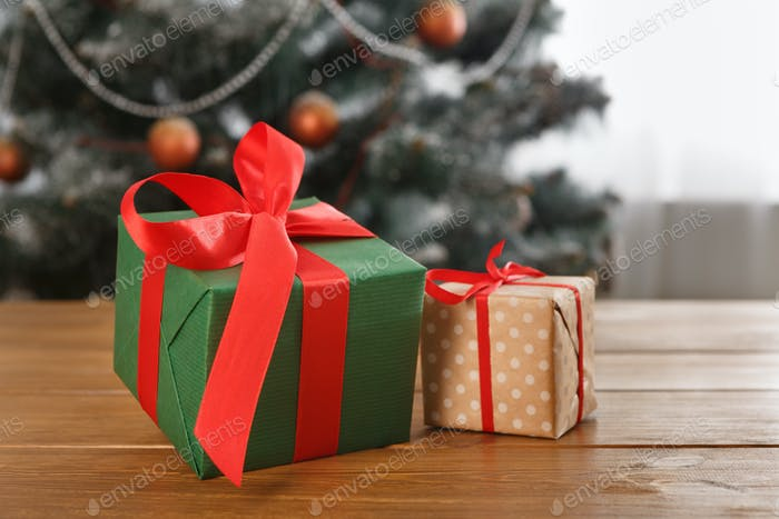 Christmas present on decorated tree background, holiday concept