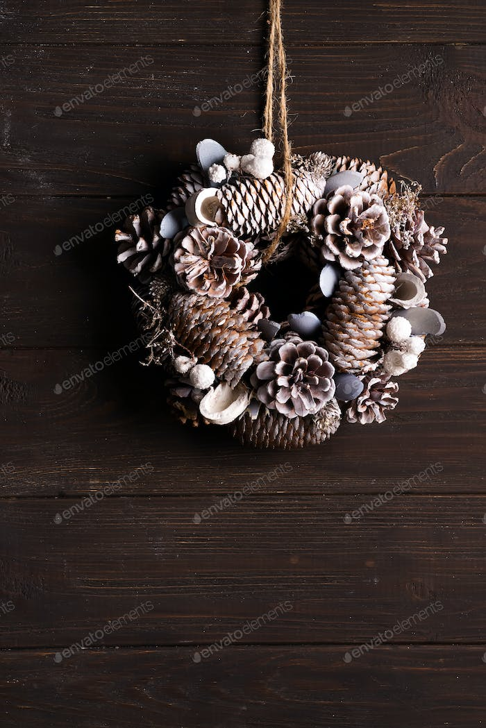 White Christmas door wreath decoration made of pine and fir cones on dark wooden background, copy