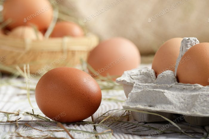 Raw organic brown chicken eggs in eco friendly paper carton on w