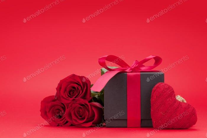 Valentinstagskarte mit Geschenkbox und Rosenblüten