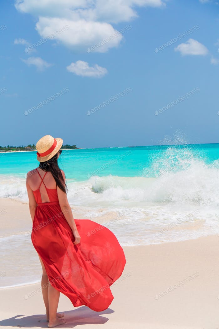 Young beautiful woman in red dress on tropical seashore