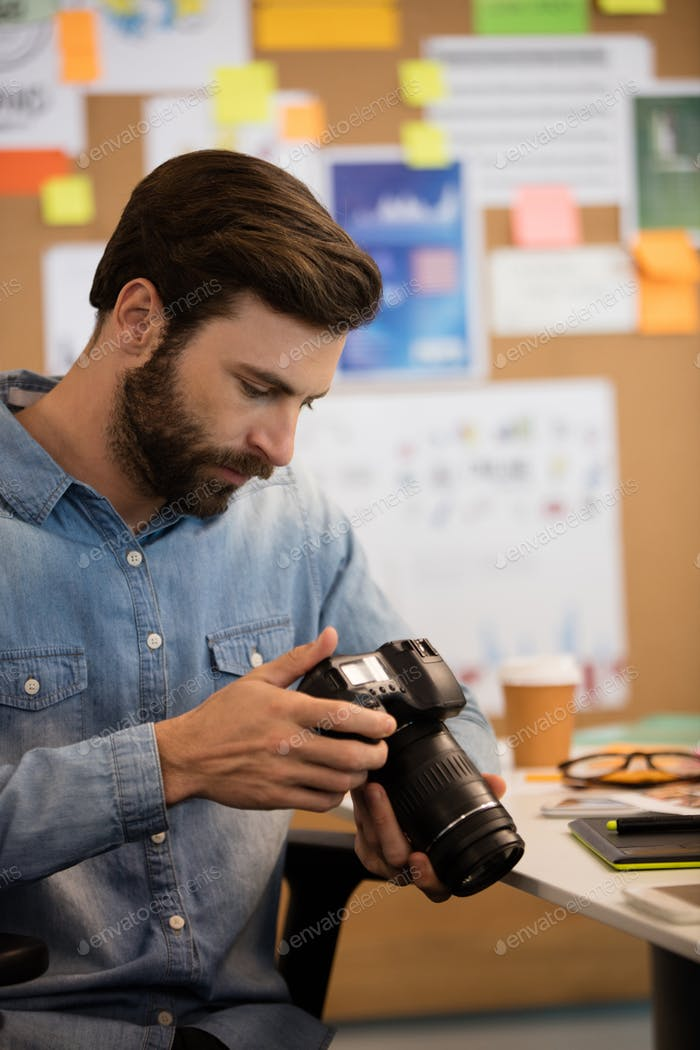 Photographer using camera in creative office